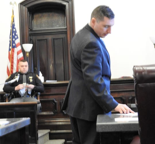 Assistant Prosecutor Ben Hall checks notes while questioning Dep. Dustin Mullinnex of the Coshocton County Sheriff's Office. Mullinnex initially investigated storage units that had been broken into last August that Chase Heath is accused of having done along with two other men.