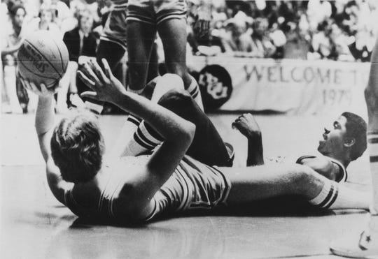"Indiana State's Larry Bird, left, lies on his back to toss the ball during a scramble with Earvin ""Magic"" Johnson, right, during NCAA Championship game in Salt Lake City, Utah, March 26, 1979."