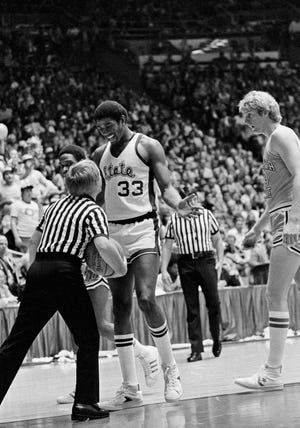 "Michigan State's Earvin ""Magic"" Johnson smiles at the referee as he gets a foul called on him during NCAA Basketball Championship game Monday, March 26, 1979 at Salt Lake City, Utah. At right is Indians State's Larry Bird."
