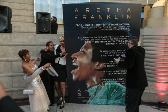 "Sabrina Owens (left) reacts with friends and ""Amazing Grace"" producer Alan Elliot during the movie's premiere at the Charles H. Wright Museum in Detroit on Monday, March 25, 2019."