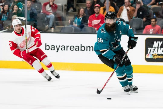 San Jose Sharks defenseman Brent Burns skates with the puck as Detroit Red Wings left wing Taro Hirose defends in the first period at SAP Center at San Jose on March 25, 2019.