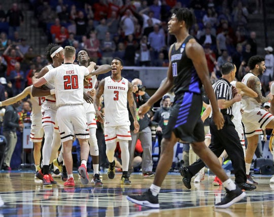 Members of Texas Tech celebrate as Buffalo's Jeenathan Williams walks past in the foreground at the end of their game last weekend.
