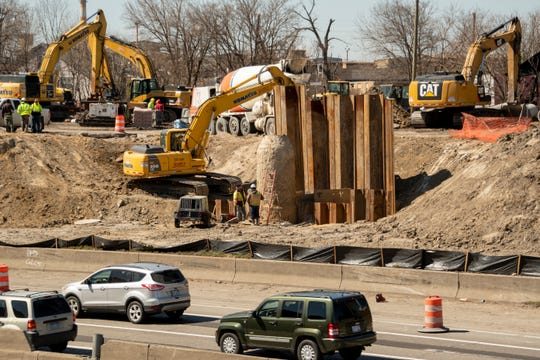 Construction crews work on the retaining wall along I-94 near Concord Avenue in Detroit, Tuesday.