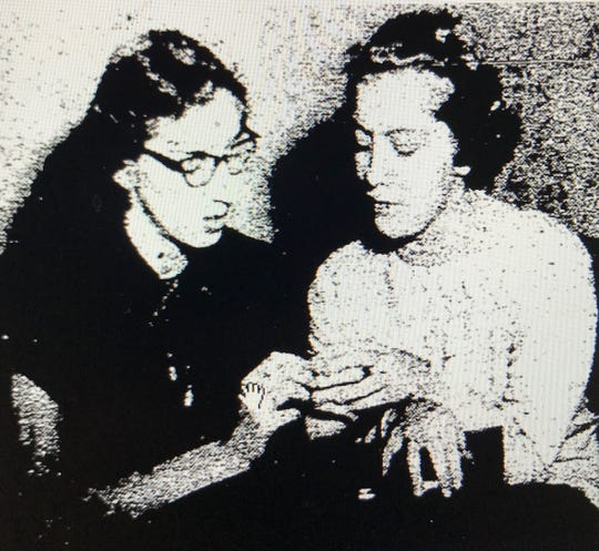 Evelyn Hirsch and Joann Vaughn examine a class ring found on the body of Andrew Reagan, an Evansville man who was killed in 1954.