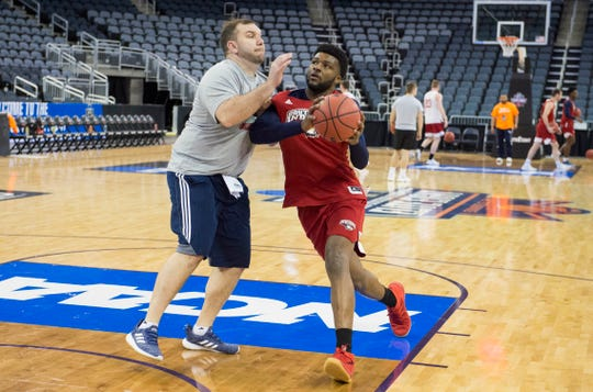 Southern Indiana's Emmanuel Little (14) drives past Southern Indiana's Assistant Coach Brent Owen during practice at the Ford Center on Tuesday before the Screaming Eagles take on the West Texas A&M Buffaloes Wednesday, March 27, 2019 in the first round of the NCAA 2019 Division II Men's Basketball Elite Eight tournament.