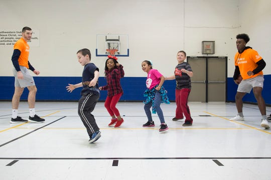 University of Southern Indiana's Jacob Norman, far left, and Kobe Caldwell, far right, run students at the YMCA's Caldwell Community Center through defensive drills during the Skills and Drills activity Tuesday, March 26, 2019. Teams in the NCAA 2019 Division II Men's Elite Eight tournament were throughout the city involved in community engagement Tuesday.