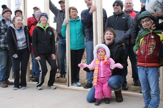 Natasha Shabalin and 2-year-old Samatha, celebrate during the wall raising of their new home at Harmony Cottages.