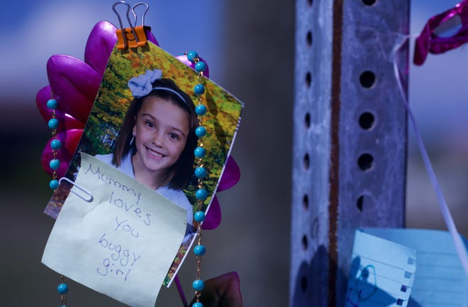 A note from mom is attached to a photograph of 8-year-old Layla Aiken at a memorial site. Layla was killed by a hit-and-run driver Monday morning.