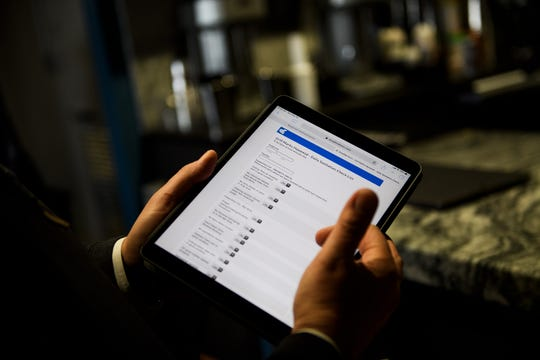 Bob Munnich goes through a checklist of sanitation requirements on his tablet at Grill Marks' Haywood Mall location Monday, March 25, 2019.