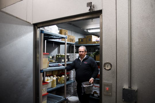 Bob Munnich removes unlabeled food containers from the refrigerator during a sanitation inspection at Grill Marks' Haywood Mall location Monday, March 25, 2019.