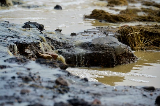 Spring snowmelt runs over East Portage Road, washing away parts of the road surface, north of Great Falls on Tuesday.  Minor flooding has caused road closures on numerous roads in Cascade and Chouteau Counties.