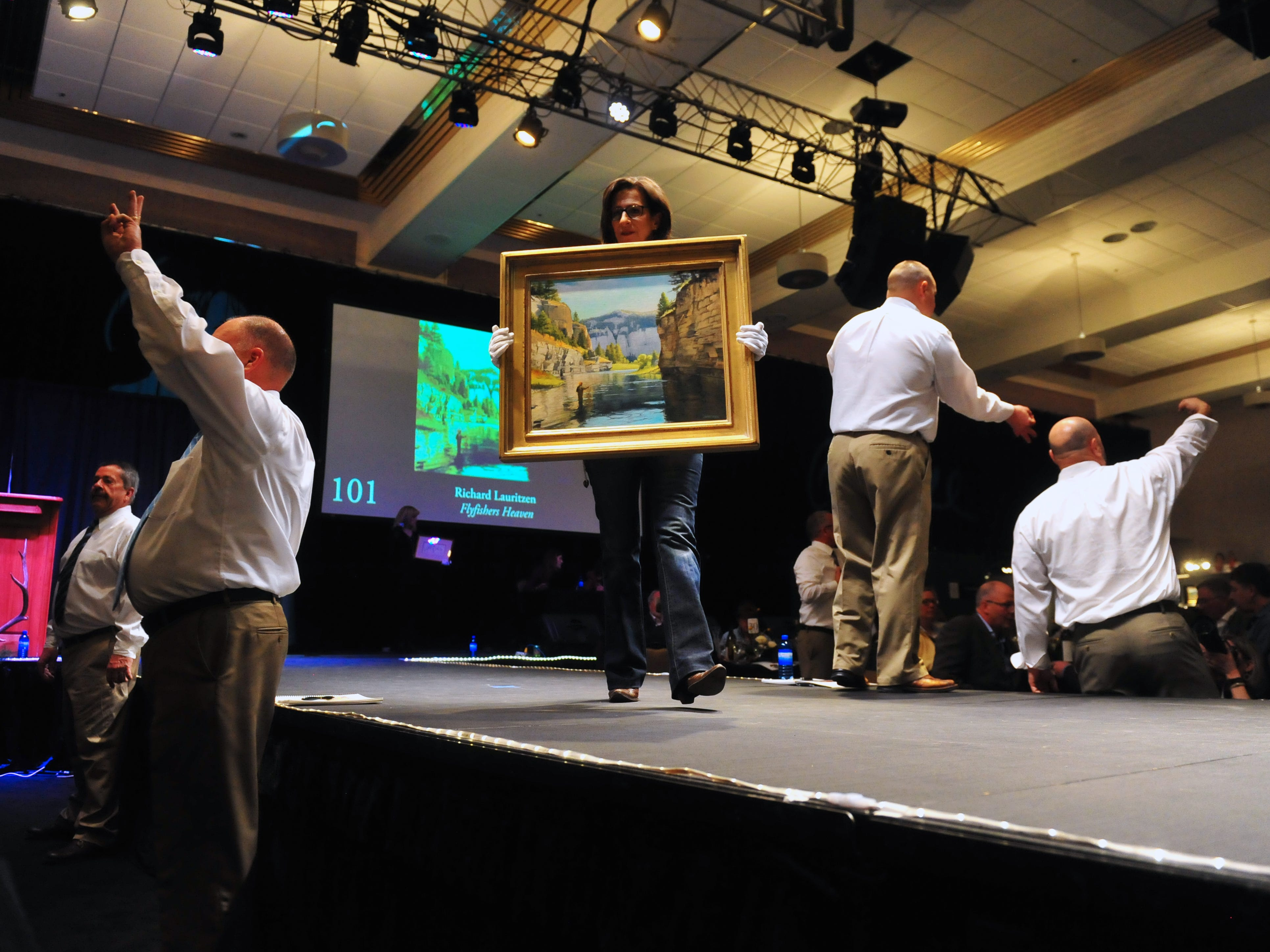 "Bidding begins on Richard Lauritzen's ""Flyfishers Heaven"" during The Russell Live Auction on Saturday night in the Great Falls Civic Auditorium."