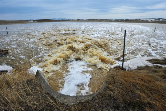 Water rushes through culvert under Highway 87 between Great Falls and Fort Benton, Tuesday.