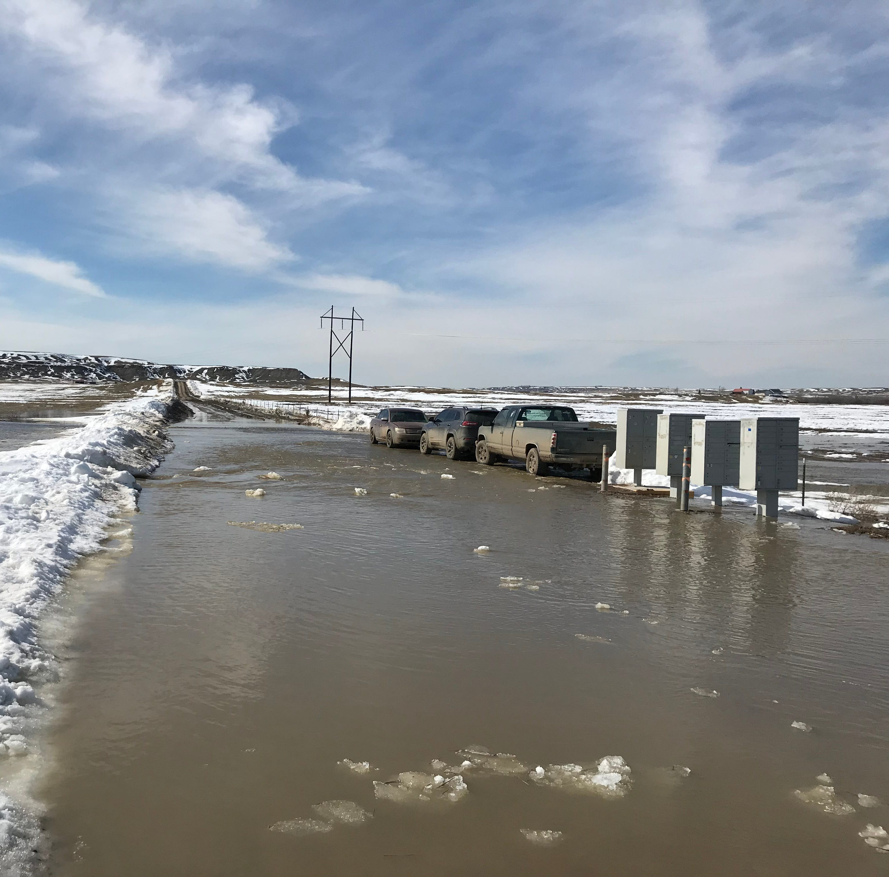 Water pouring over roads in Cascade, Chouteau Counties