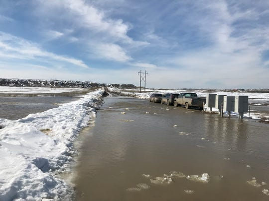 Water washes over Loch Lane off Ulm Vaughn Road Monday. Numerous roads have been washed out in Cascade and Choteau counties.