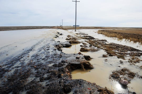 Spring snowmelt runs over East Portage Road north of Great Falls on Tuesday.  Minor flooding has caused closures on numerous roads in Cascade and Chouteau Counties.