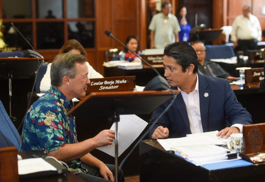 Sens. James C. Moylan, left, and Wil Castro converse during a session recess at the Guam Congress Building, March 26, 2019.