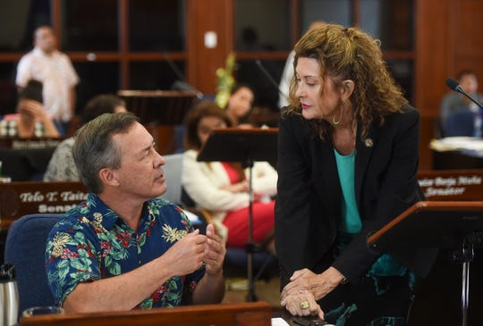 Sens. James C. Moylan and Kelly Marsh in a discussion during a session recess at the Guam Congress Building, March 26, 2019.
