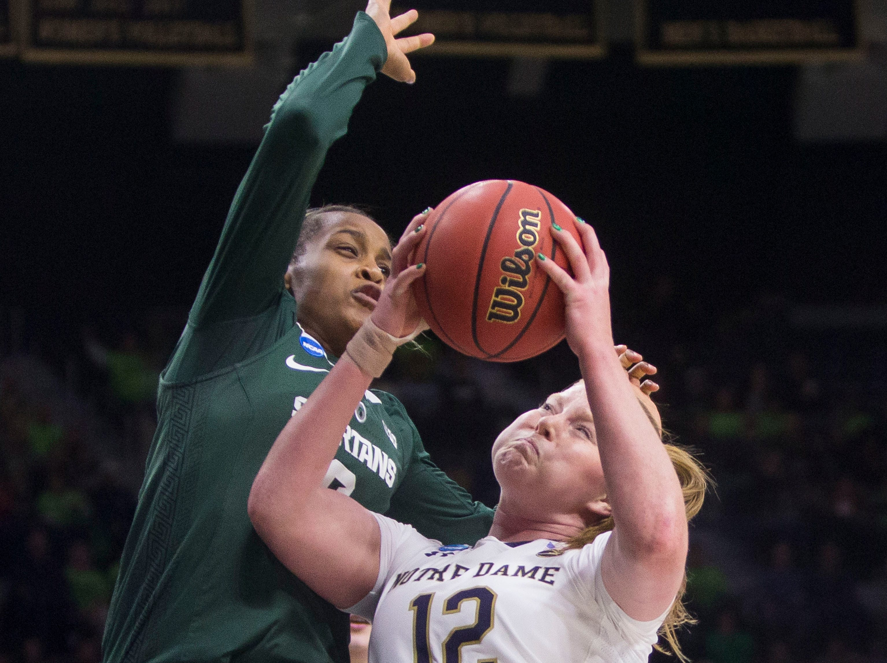 Notre Dame's Abby Prohaska (12) goes up to shoot under pressure from Michigan State's Shay Colley during a second-round game in the NCAA women's college basketball tournament in South Bend, Ind., Monday, March 25, 2019. (AP Photo/Robert Franklin)