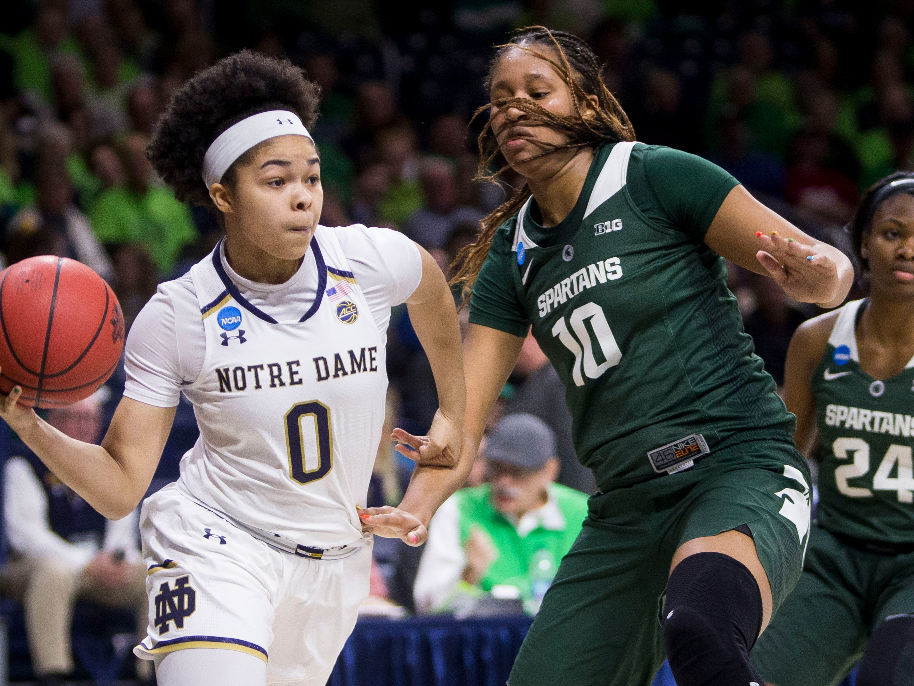 Notre Dame's Jordan Nixon (0) passes around Michigan State's Sidney Cooks (10) during a second-round game in the NCAA women's college basketball tournament in South Bend, Ind., Monday, March 25, 2019. (AP Photo/Robert Franklin)