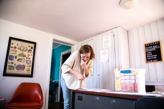 Sarah Ziegenhorn, founder and executive director of the Iowa Harm Reduction Coalition, talks on the phone while trying to pay a bill on Monday, March 18, 2019, inside their office at 1216 2nd Ave. SE in Cedar Rapids, Iowa.