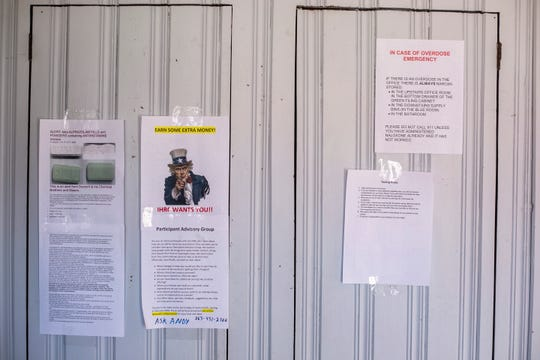 Informational pieces of paper hang from a cabinet in the front room of the Iowa Harm Reduction Coalition on Monday, March 18, 2019, inside their office at 1216 2nd Ave. SE in Cedar Rapids, Iowa.