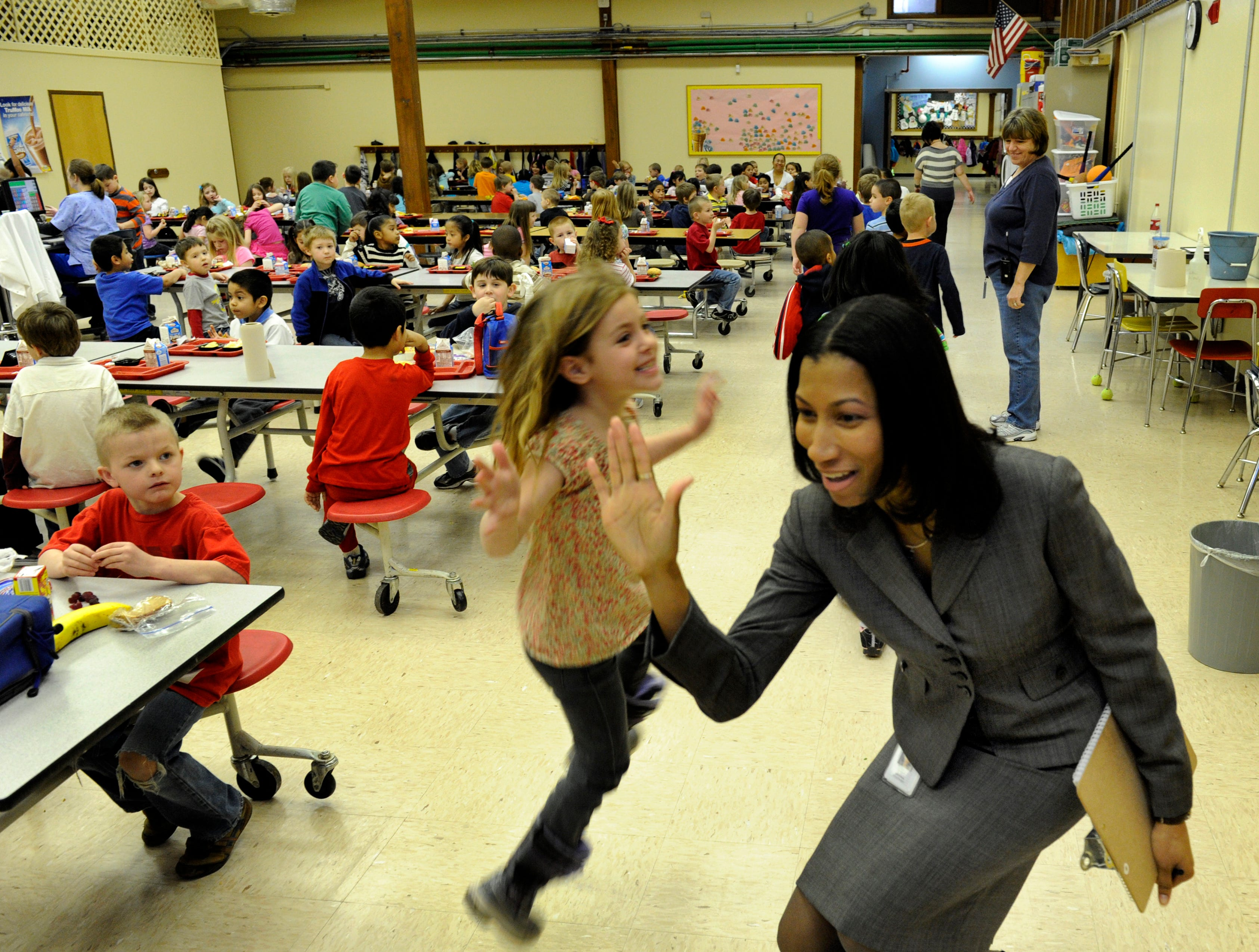 News Sentinel reporter Lydia McCoy gives a high-five to Trinity Brown as they pass each other in the lunchroom Tuesday, Feb. 28, 2012 at Adrian Burnett Elementary School. McCoy was serving as Principal for the Day at the North Knoxville school. McCoy spent the day talking to students and observing classroom activities and she had talked at length to Brown in her classroom.