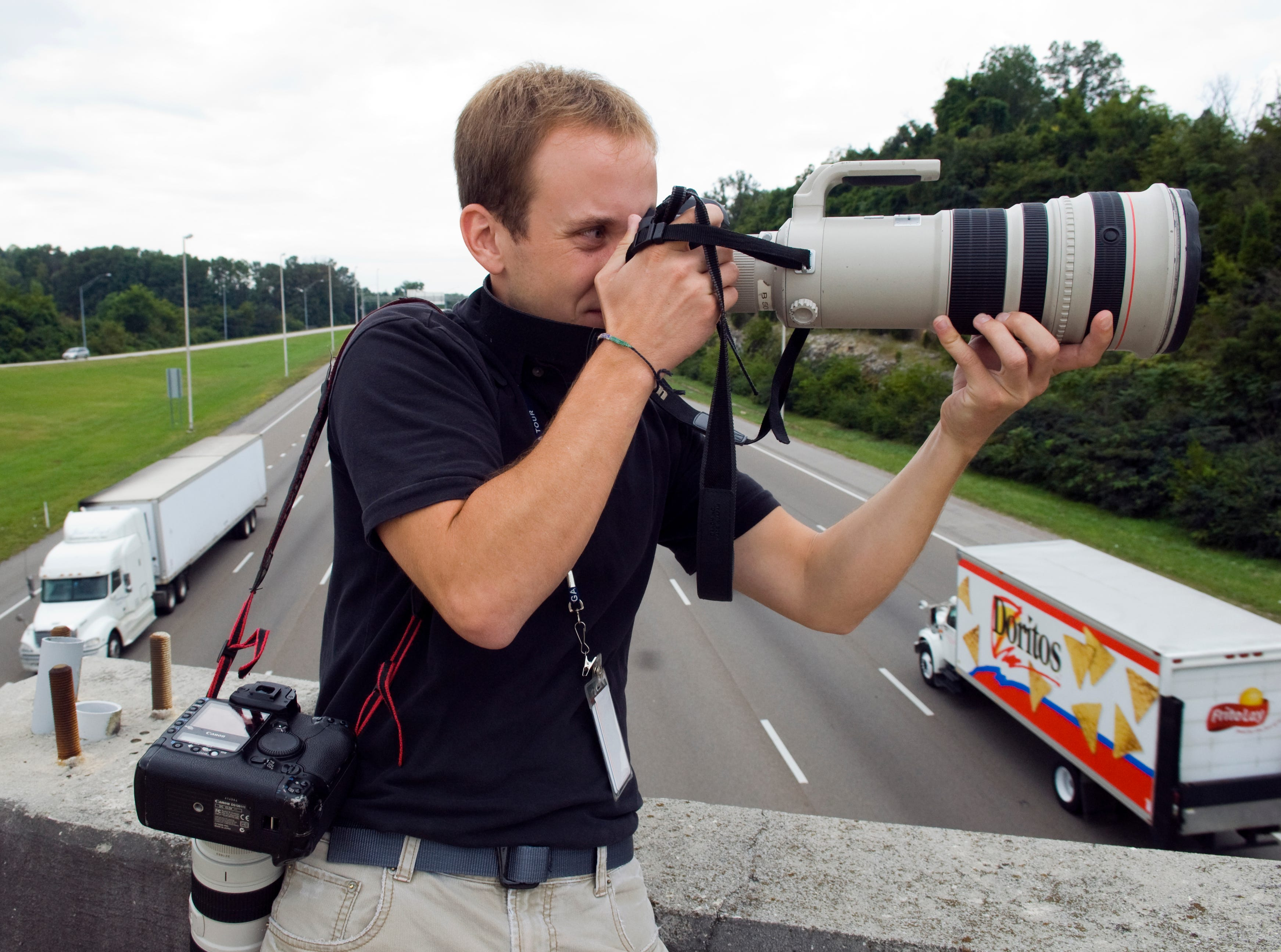 Knoxville News Sentinel staff photographer, Adam Brimer, 24, takes a picture at a spot news event with a Canon 5d Mark 2 with a 500mm lens on Tuesday, September 1, 2009.Brimer  photographs Knoxville Police Department officers as they investigate the Gap Road overpass where a man jumped off of onto interstate 640 earlier on Tuesday.
