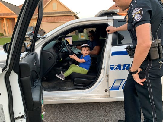 "New ""officer"" Brigsby Langford, 2, gets a closer look at a police car thanks to two patrolling Broussard Police officers."