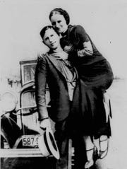 Bank robbers Clyde Barrow and Bonnie Parker pose with their car in the 1930s.
