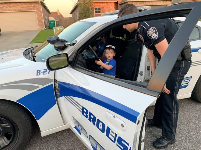 """New """"officer"""" Brigsby Langford, 2, gets a closer look at a police car thanks to two patrolling Broussard Police officers. The officers let Brigsby """"drive."""""""
