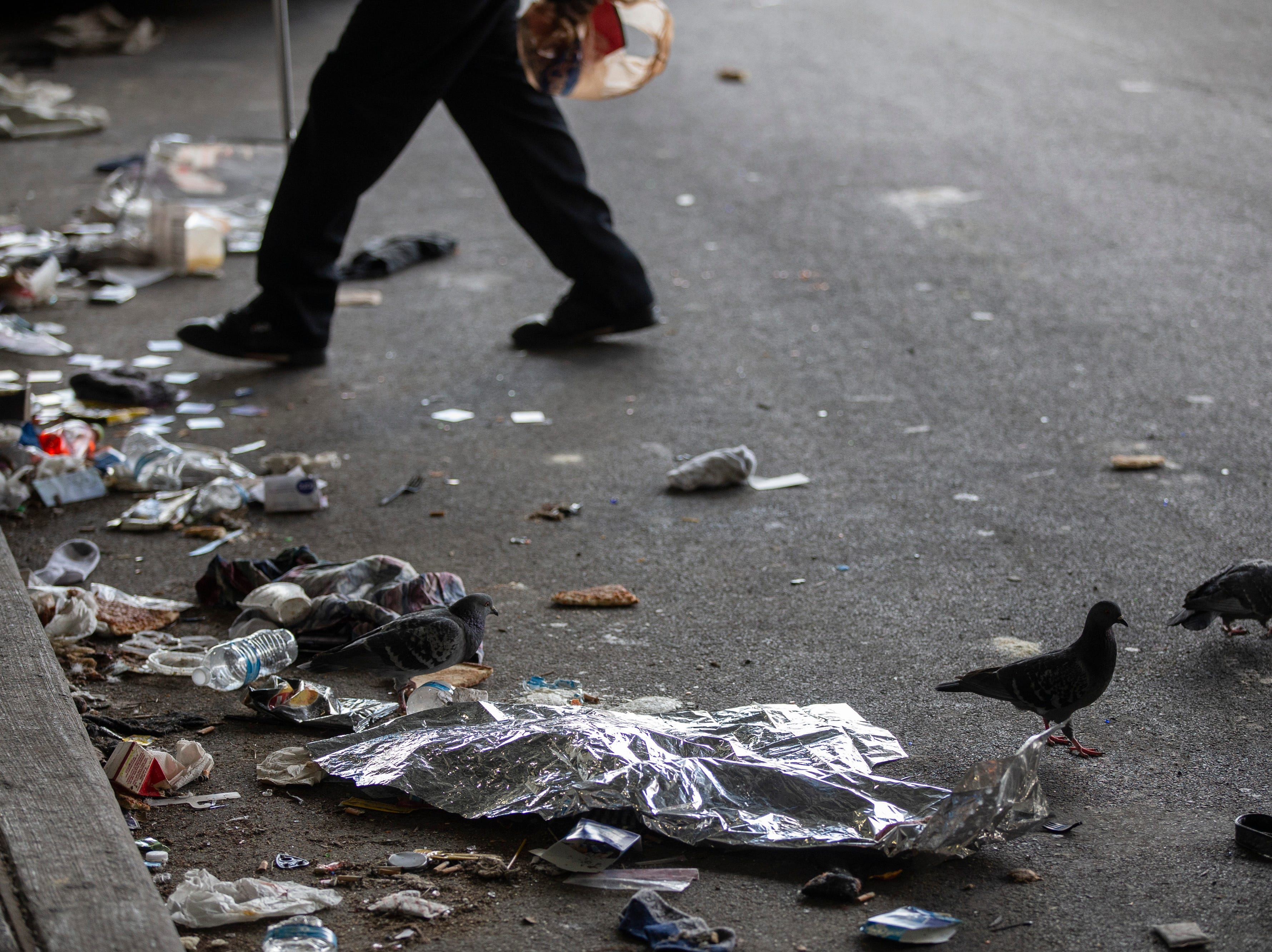 Residents move past pigeons and trash at the homeless camp area under the bypasses along East Jefferson Street and Jackson Street in downtown Louisville. March 18, 2019