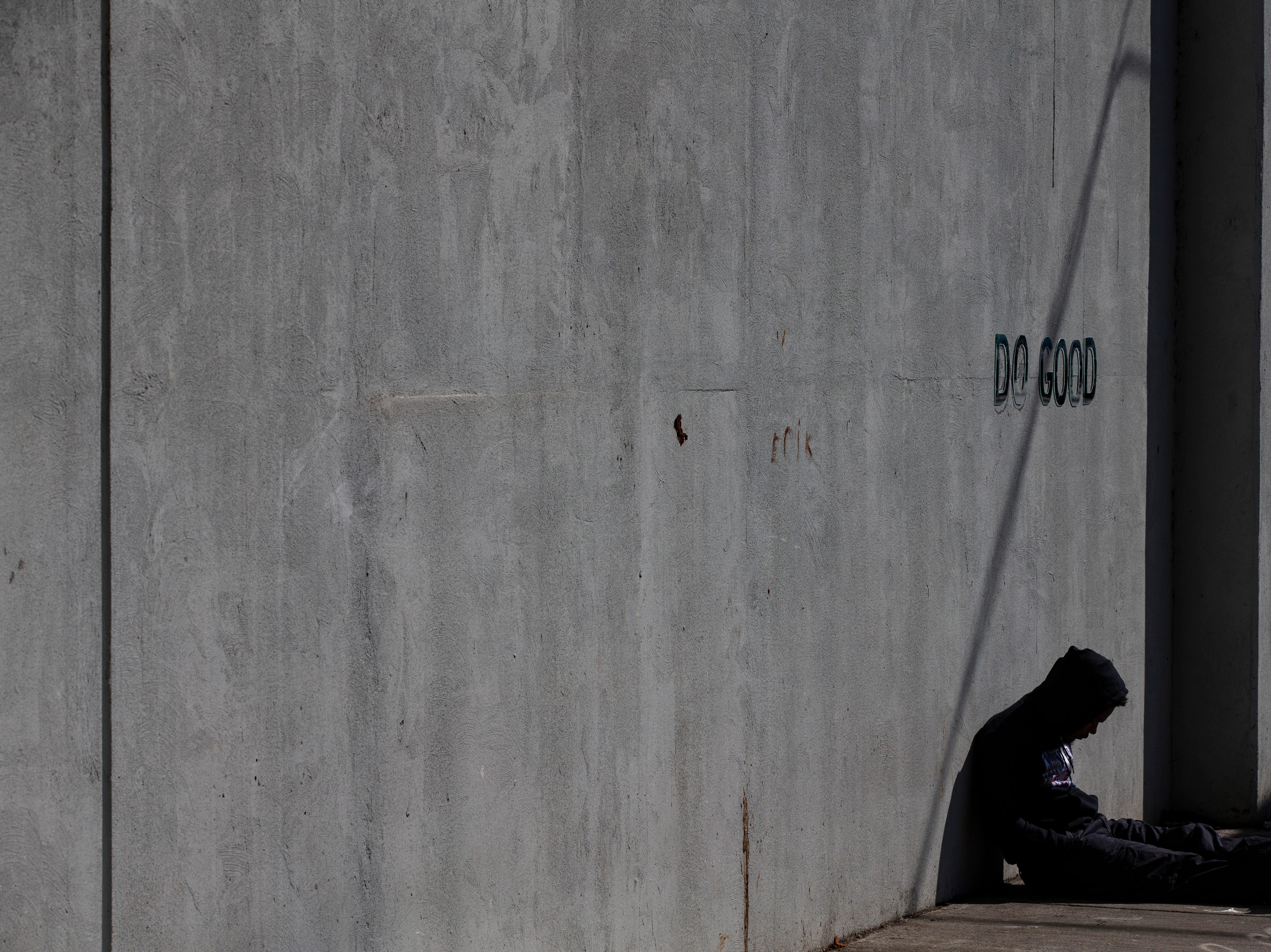 A homeless resident rest against the wall at the homeless camp area under the bypasses along East Jefferson Street and Jackson Street in downtown Louisville. March 18, 2019
