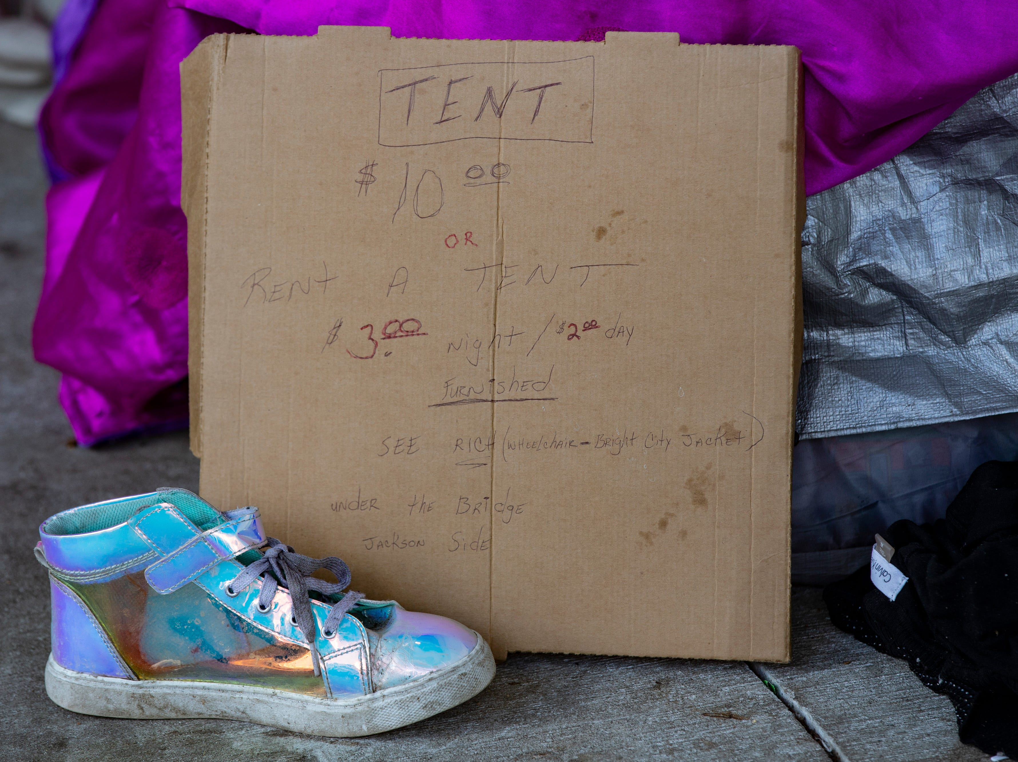 A sign for a tent purchase, or rental at the homeless camp area under the bypasses along East Jefferson Street and Jackson Street in downtown Louisville. March 18, 2019