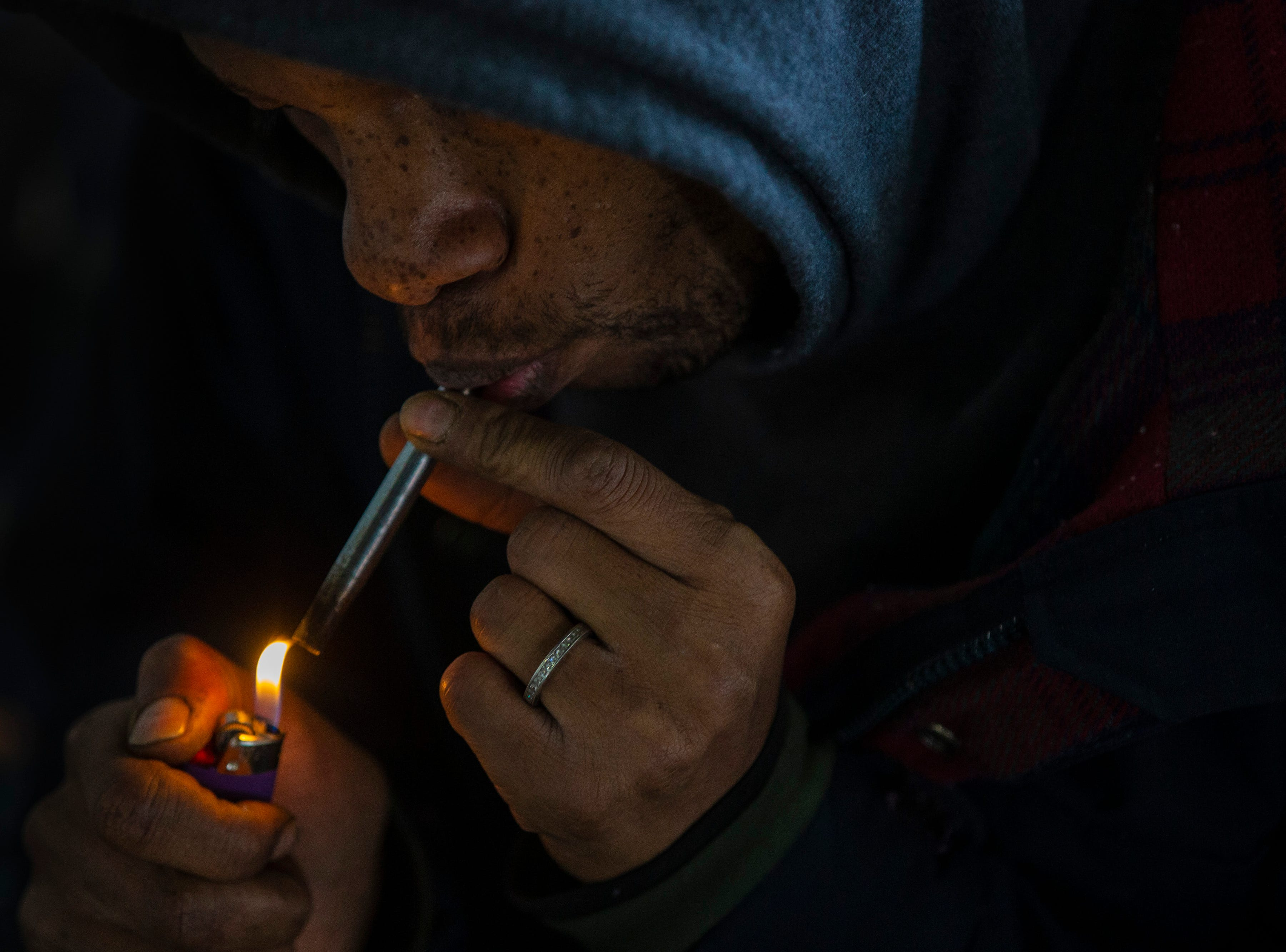 A homeless man uses a metal pipe to smoke at the homeless camp area under the bypasses along East Jefferson Street and Jackson Street in downtown Louisville. March 18, 2019