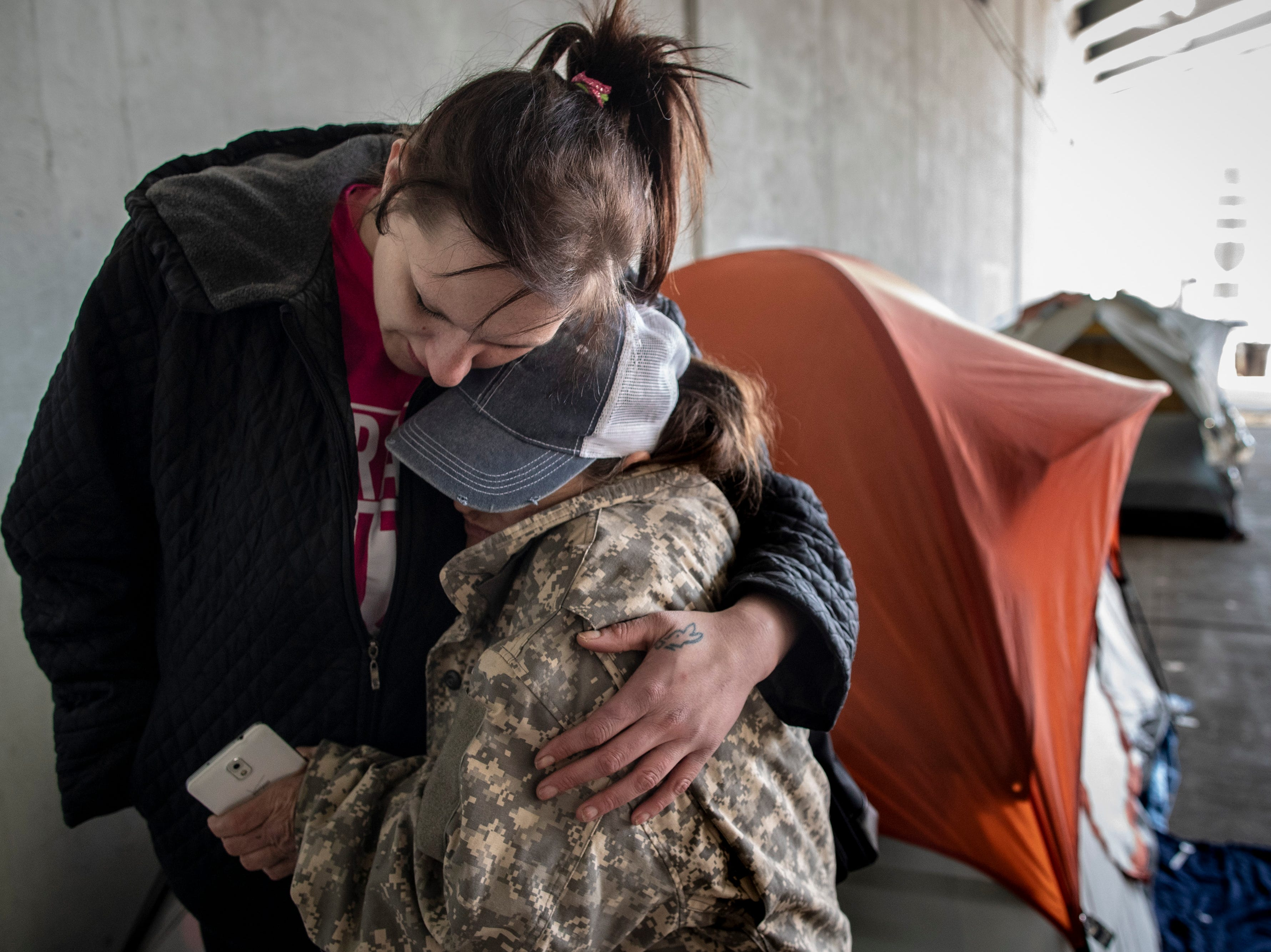 """Amanda Mathews, left, gets a hug from fellow homeless resident Candace Curry at the homeless camp area under the bypasses along East Jefferson Street and Jackson Street in downtown Louisville. Mathews has been homeless for a year after losing the love of her life and her mother within a span of a few months. """"I came to Louisville and totaled my car,"""" Mathews said. """"I'd never been homeless. I'd never been hungry before. It's definitely changed me personally."""" March 18, 2019"""