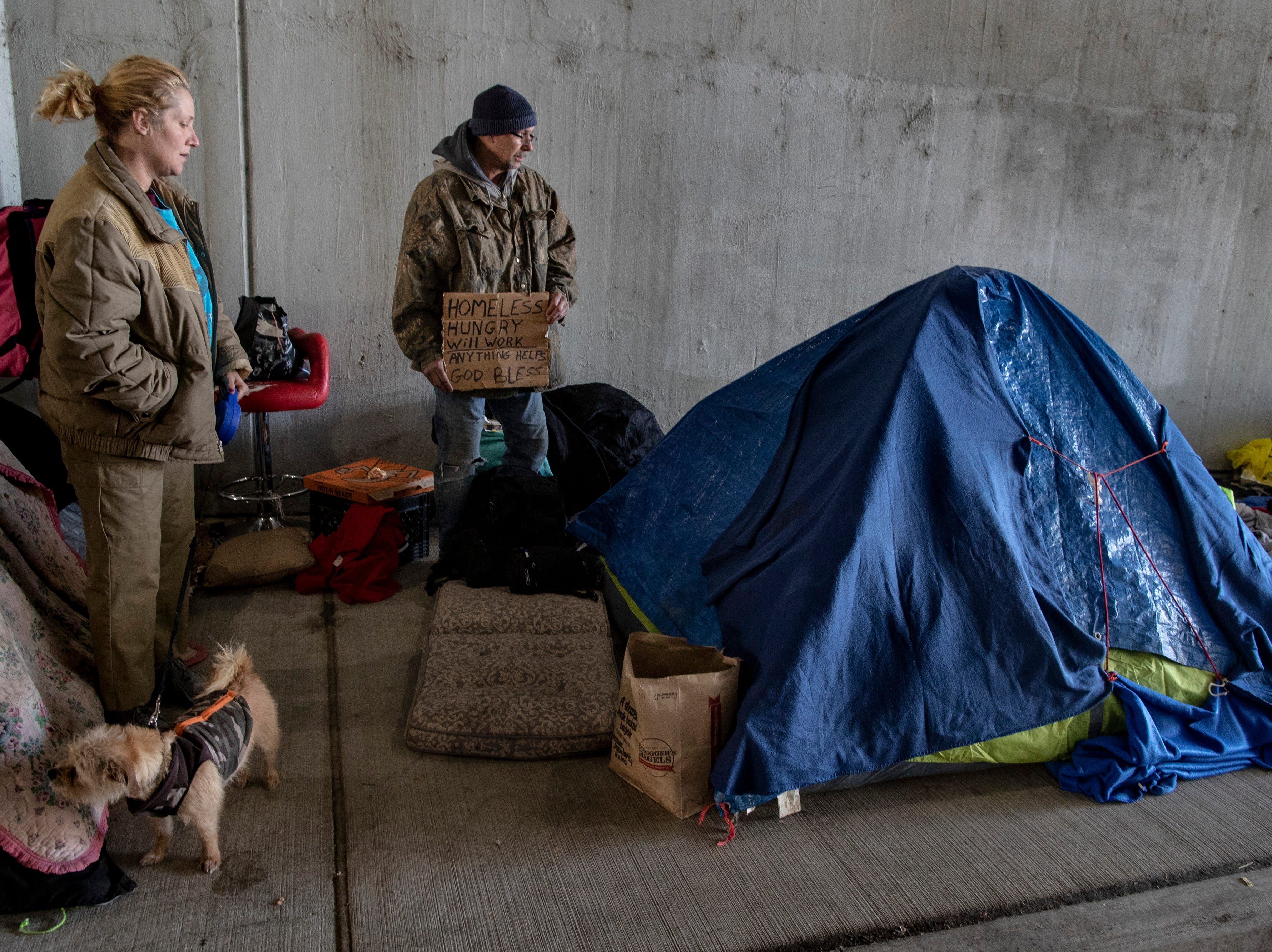 """Dani Crip, left, and her partner Jeff Weston stand near their tents at the homeless camp area under the bypasses along East Jefferson Street and Jackson Street in downtown Louisville. The couple has been homeless with their son for two years. """"I came here thinking we'd make a killing, but instead we made a lot of mistakes,"""" Weston said. Weston was a commercial painter, but suffers from the late stages of sclerosis. March 18, 2019"""