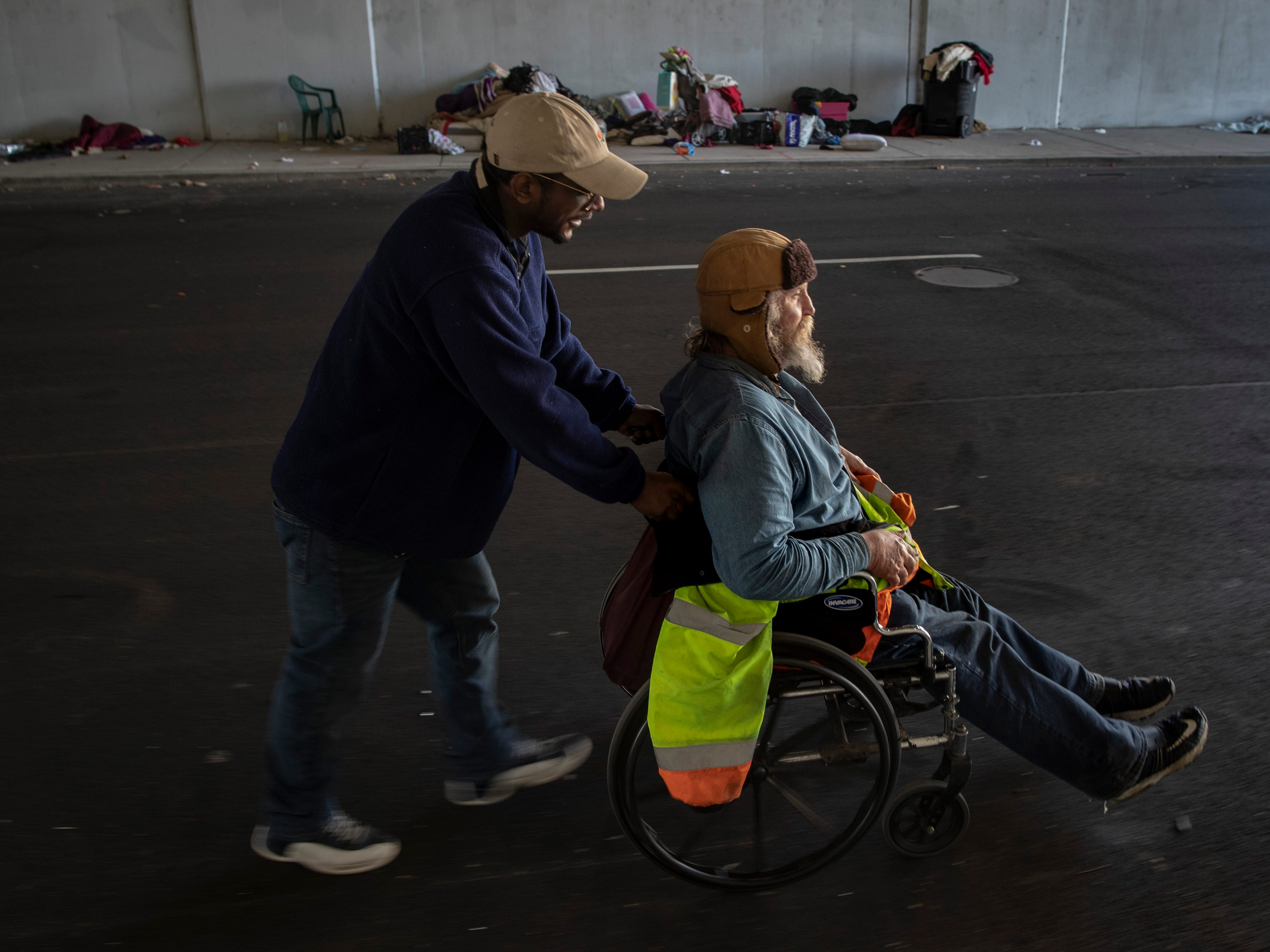 """Timothy, left, pushes his friend Richard Greene in his wheelchar at the homeless camp area under the bypasses along East Jefferson Street and Jackson Street in downtown Louisville. """"I've been homeless seven months and three weeks,"""" Greene said. """"I was hit by a car and it ruined my life."""" March 18, 2019"""