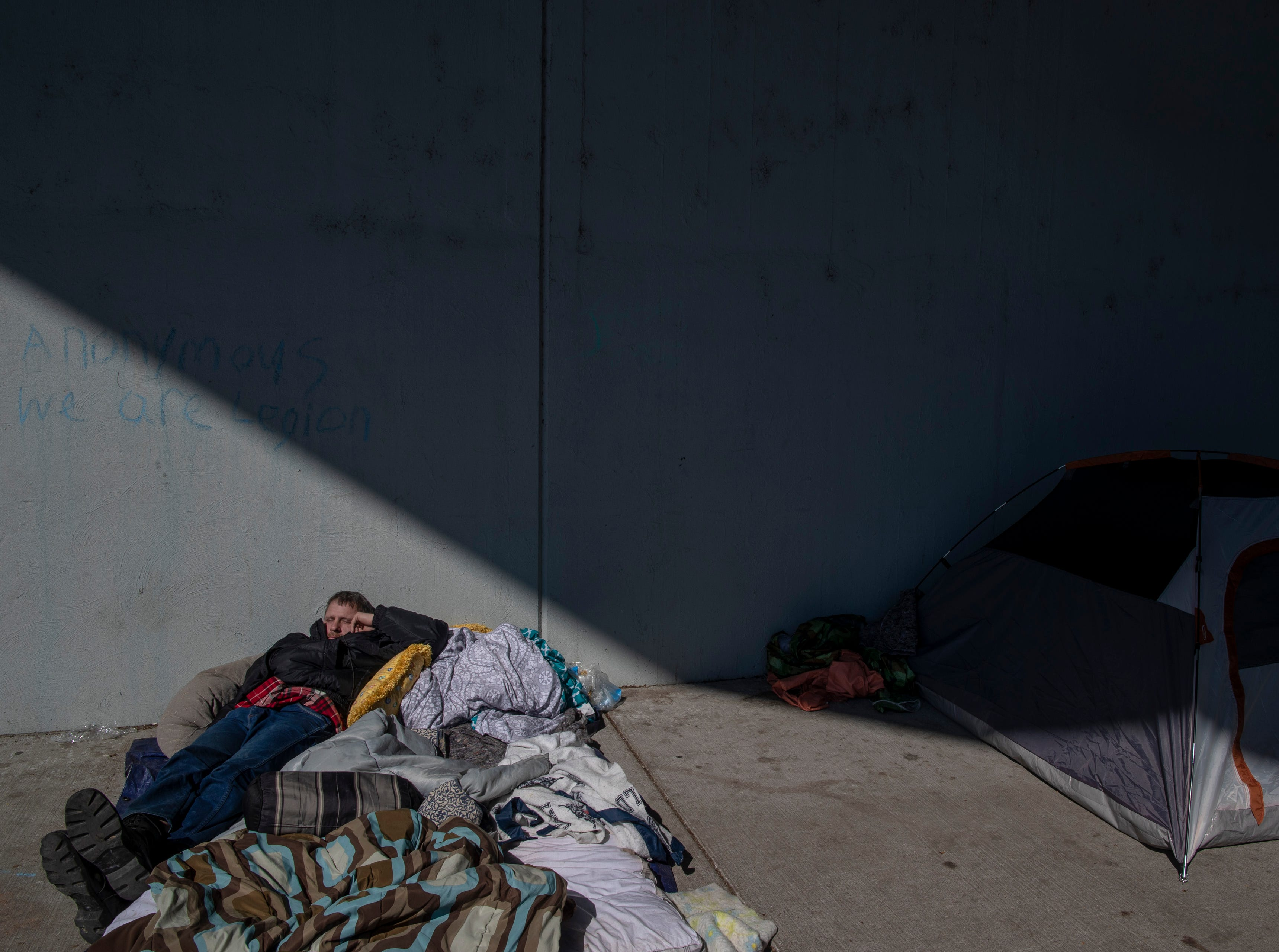 Brian Hall takes a nap at the homeless camp area under the bypasses along East Jefferson Street and Jackson Street in downtown Louisville. March 18, 2019