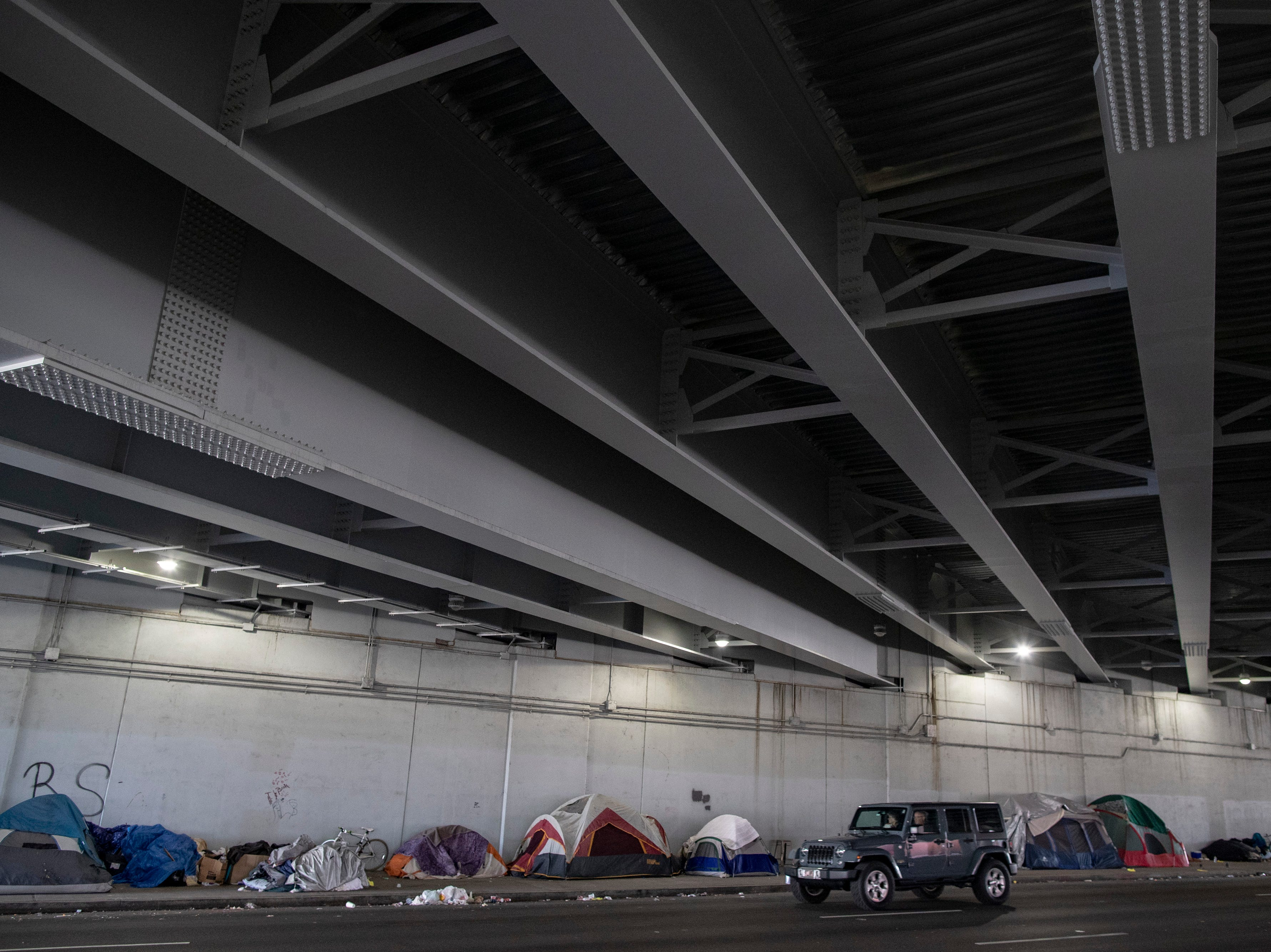 A motorist passes by the homeless camp area under the bypasses along East Jefferson Street and Jackson Street in downtown Louisville. March 18, 2019