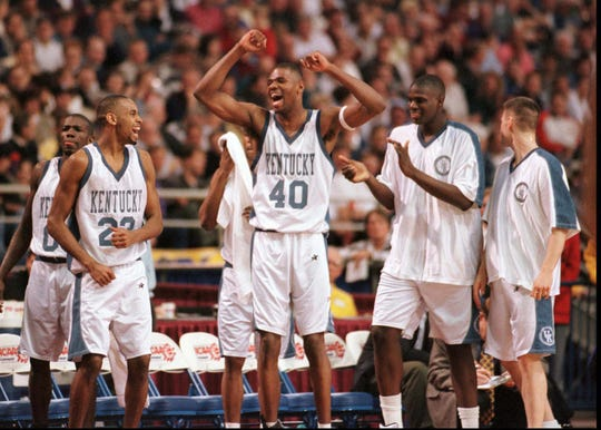 Players on the Kentucky bench, including Walter McCarty, center, Derek Anderson, front left, and Tony Delk, rear left, celebrated during their game against Utah in the NCAA Midwest Regional final at the Metrodome in Minneapolis on March 21, 1996.