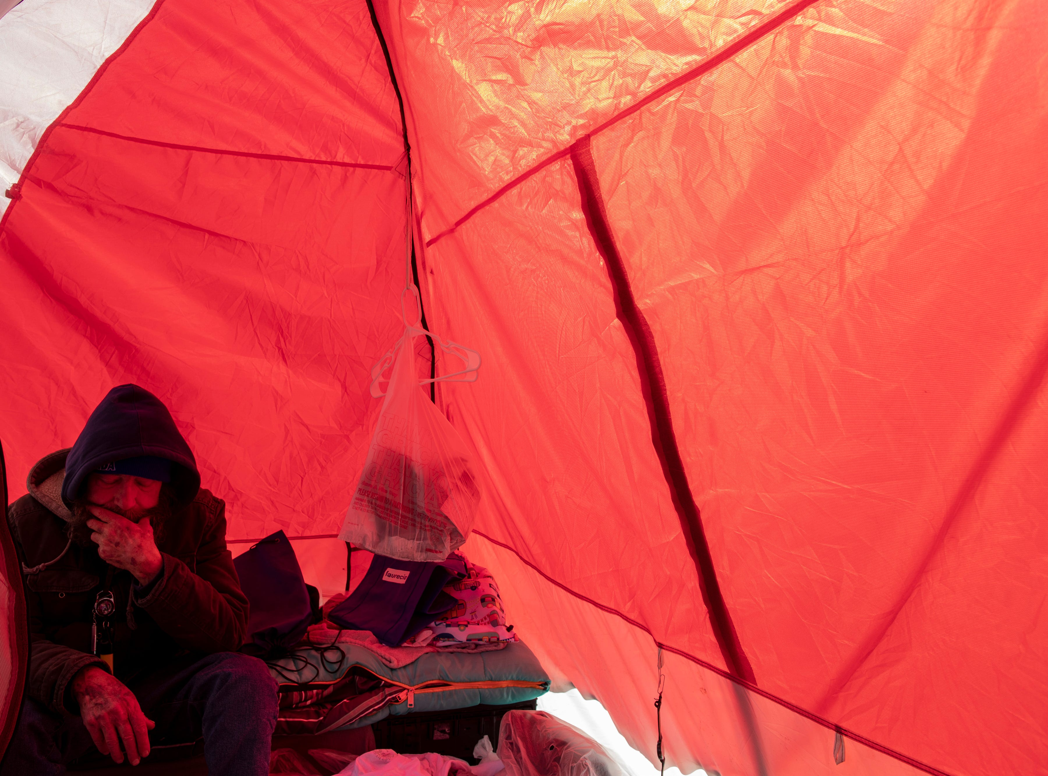 """Mitchell Sneed sits inside his tent at the homeless camp area under the bypasses along East Jefferson Street and Jackson Street in downtown Louisville. """"I'm not surprised they want everyone gone,"""" Sneed said. """"You look around and you see how trashy people are."""" March 18, 2019"""