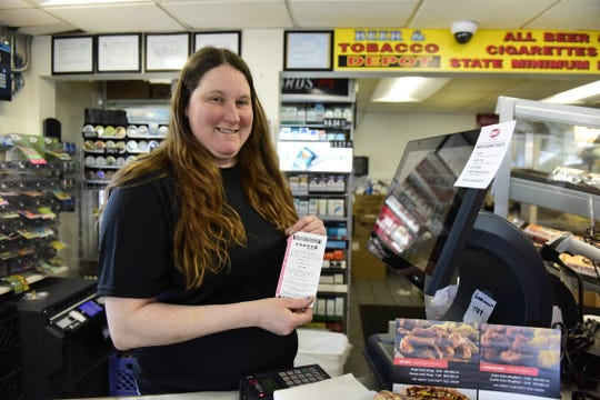 Brandy Nichols, manager of the Marathon station between Galion and Crestline, holds a freshly printed Powerball ticket Tuesday morning.