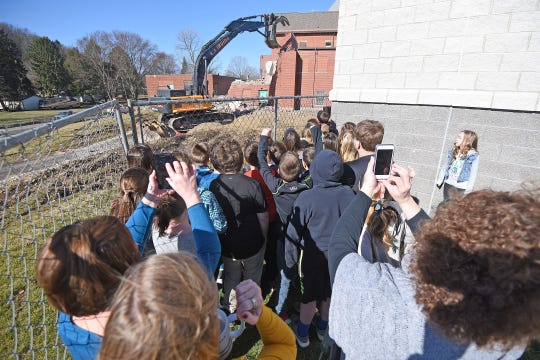 Bellville students cheer as their former school building is knocked down as demolition began on Tuesday morning.  Demolition is expected to take four to six weeks, with an additional four weeks to haul everything away.