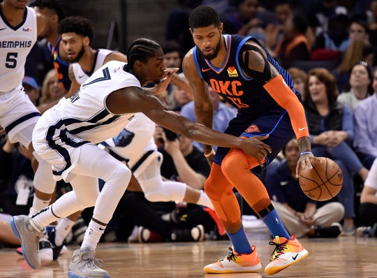 Oklahoma City Thunder forward Paul George (13) handles the ball against Memphis Grizzlies forward Justin Holiday (7) during the first half of an NBA basketball game Monday, March 25, 2019, in Memphis, Tenn. (AP Photo/Brandon Dill)