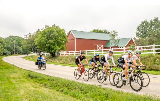 Jens Vogt (middle), retired professional racer and Tour de France announcer, rides with a group of other riders during the Ride Across Wisconsin. Jens is a chatty crowd favorite at RAW every year.
