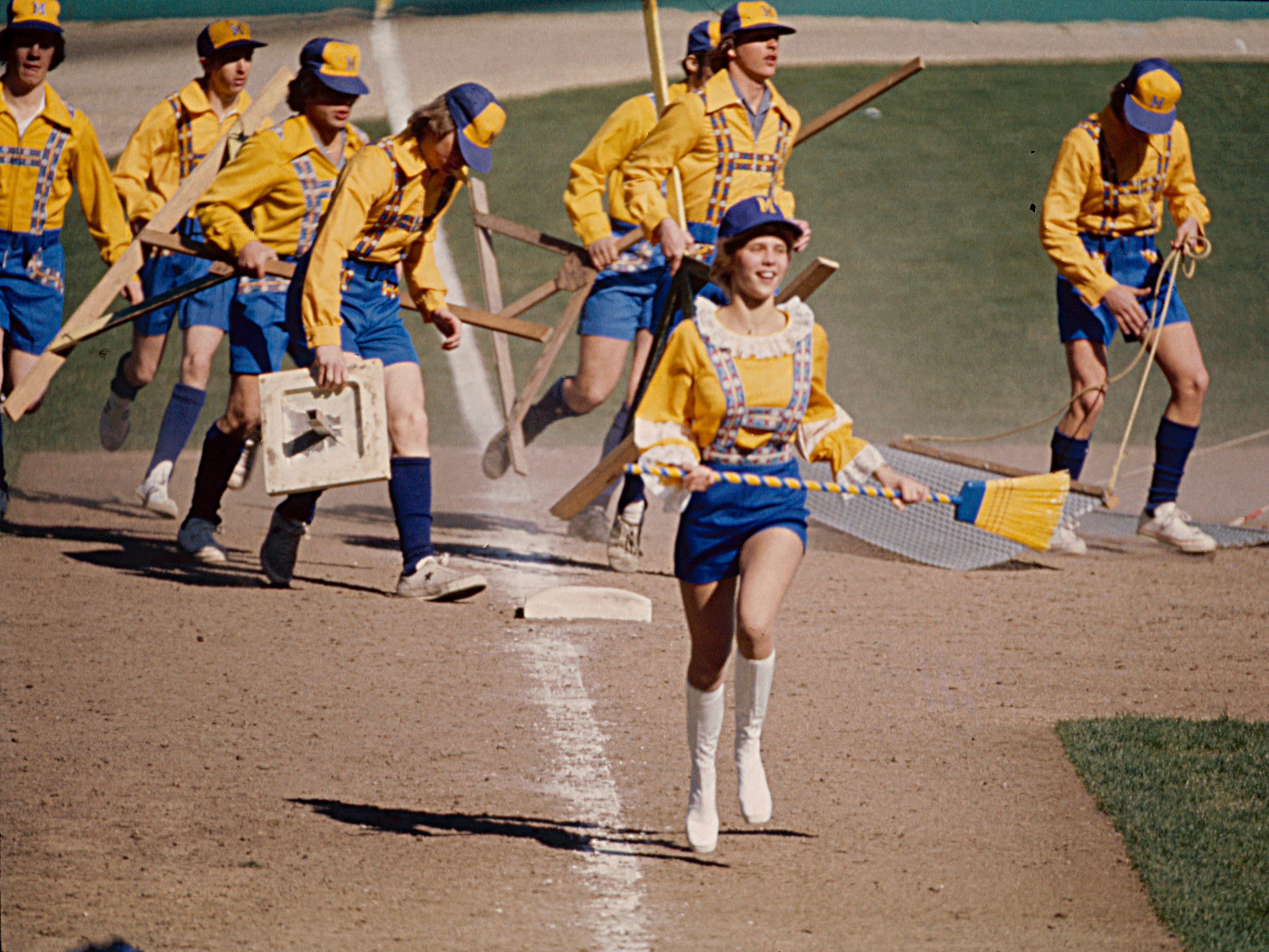 Bonnie Brewer (a.k.a. Janine Feltz) leads the grounds crew during their mid-game infield cleanup detail on opening day at County Stadium on April 8, 1976. This photo was published in the April 9, 1976, Milwaukee Journal. In the home opener, the Milwaukee Brewers beat the New York Yankees, 5-0.