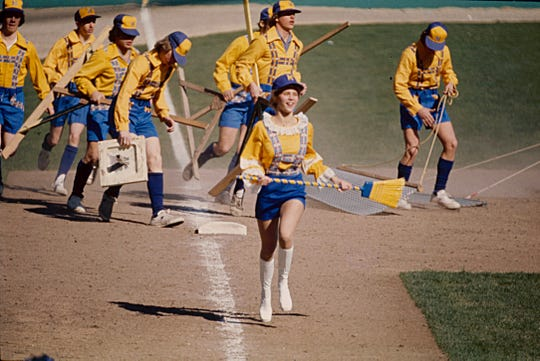 Bonnie Brewer (Janine Feltz) leads the grounds crew during mid-game infield cleanup on Opening Day in 1976.