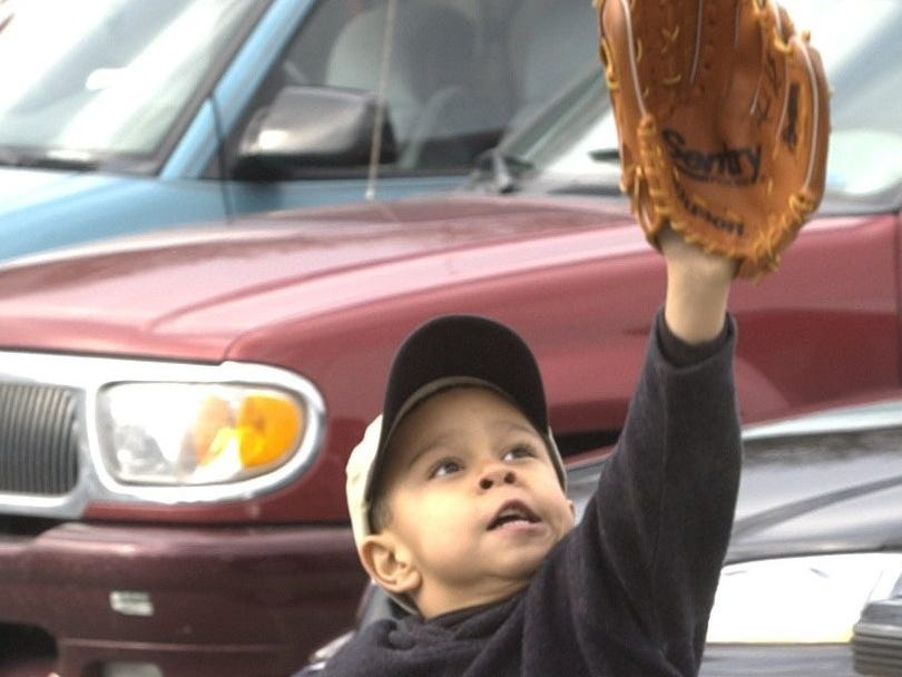 Conner Claiborne of Whitefish Bay, plays catch with his father, Phil, in the parking lot outside Miller Park before the Milwaukee Brewers' home opener on April 5, 2002. The Brewers beat the Arizona Diamondbacks, 6-2.