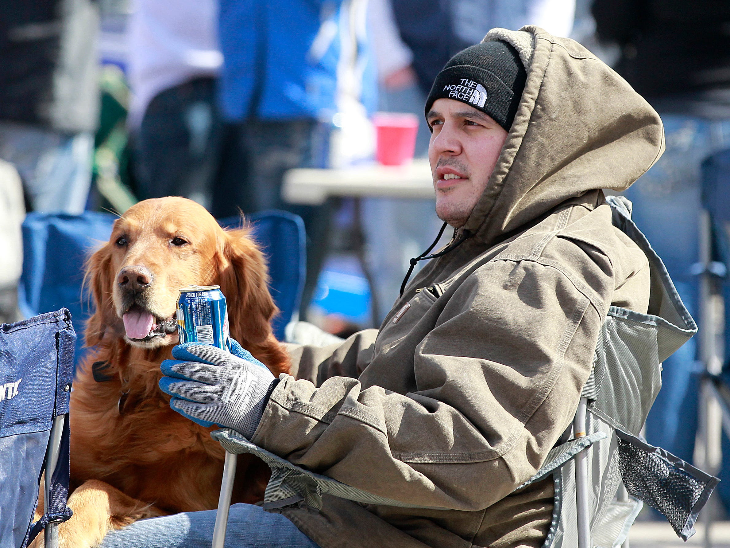 Joshua Vianes bonds with Chance, a friend's dog, while tailgating in the parking lot at Miller Park on opening day, on April 1, 2013. Inside the stadium, the Milwaukee Brewers beat the Colorado Rockies, 5-4.